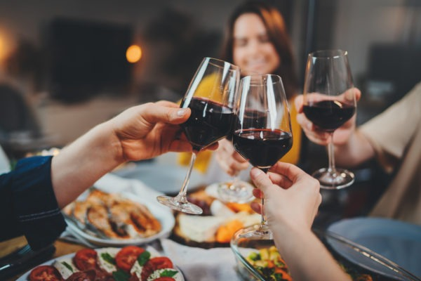 Group of people celebrating anniversary at home, cozy atmosphere, family dining at restaurant with healthy food making cheers with wine glasses, Togetherness Friendship Traditional concept